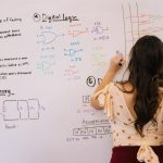 This is an image of a woman doing math on a white board.