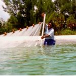 This is a picture of a teenage oceanographer using a sieve net to identify fish inhabiting the area.