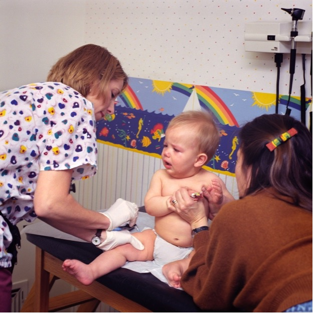 This image shows a physician assistant administering a vaccine to an infant..